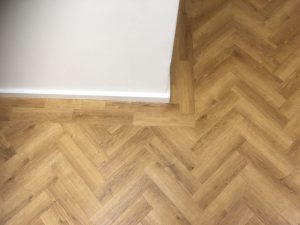 Wood effect luxury vinyl tile laid herringbone with a border